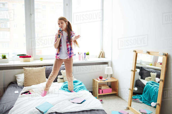 Cute teenage girl with mike singing in bedroom Royalty-free stock photo