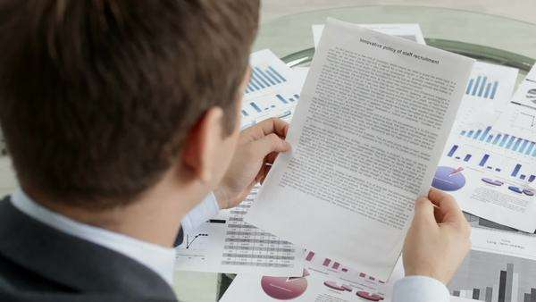 Office worker looking through important documents and reports Royalty-free stock video