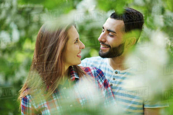Young dates looking at one another in blooming park Royalty-free stock photo