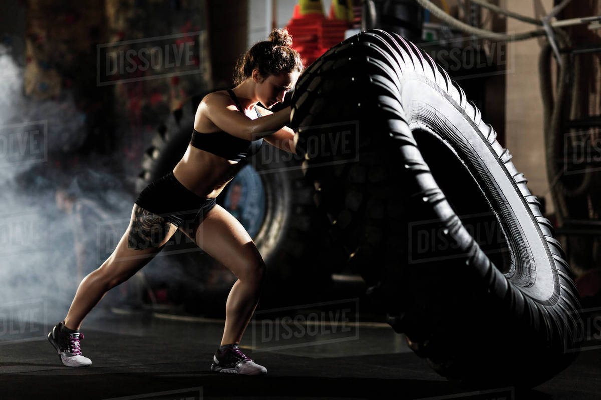Strong fit woman flipping tire in gym Royalty-free stock photo