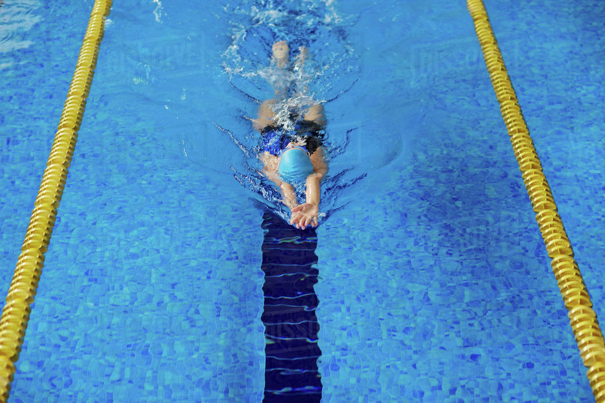 Swimming young woman training in pool - Stock Photo - Dissolve