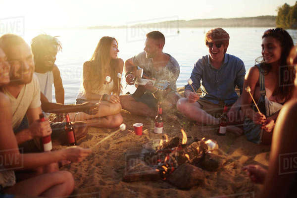 Young people spending evening on sandy beach Royalty-free stock photo