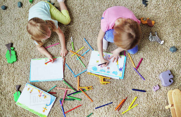 Little sisters drawing and coloring pictures in kindergarten Royalty-free stock photo