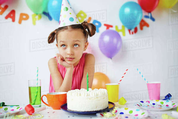 Cute girl making wish by birthday cake Royalty-free stock photo