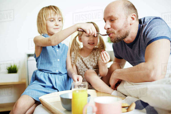 Little girl feeding her dad from spoon in the morning of father day Royalty-free stock photo