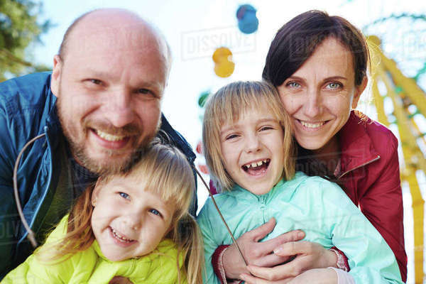 Cheerful parents and daughters looking at camera outdoors Royalty-free stock photo