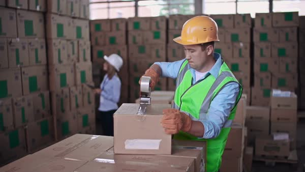 Close up of worker packing merchandise while female auditor taking inventory Royalty-free stock video