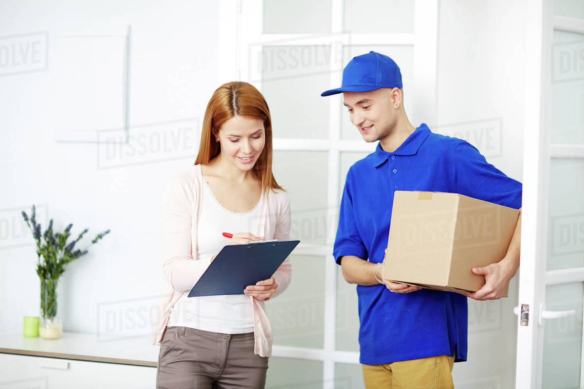 young delivery man looking at attractive young woman signing for