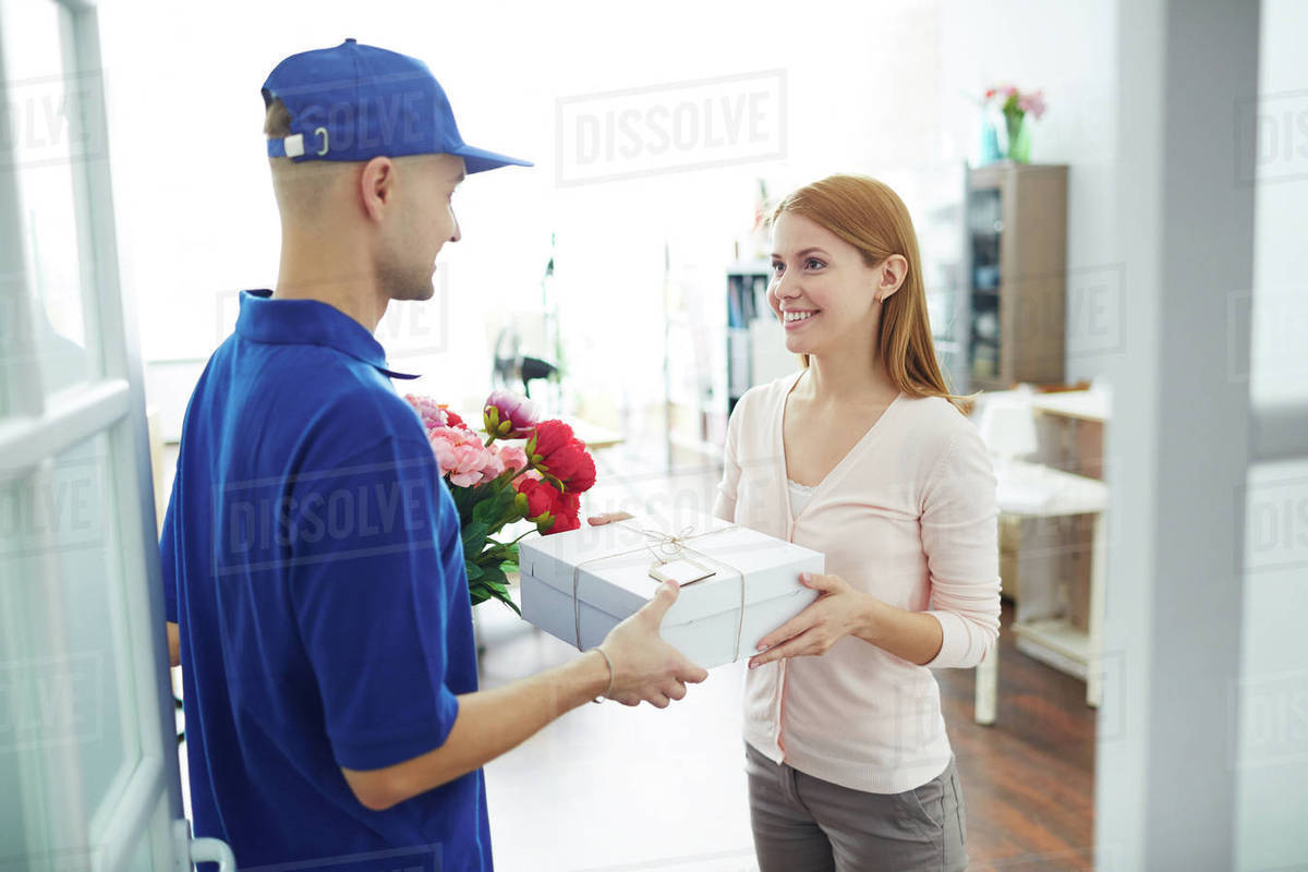 young woman receiving gift box and flowers from delivery man stock