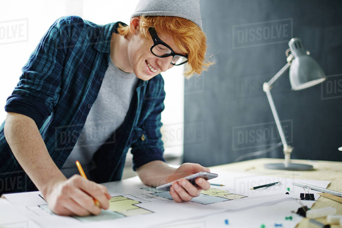 Young designer or architect using smartphone while drawing sketch Royalty-free stock photo