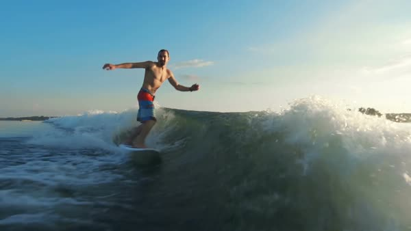 Handsome man approaching camera riding surfboard Royalty-free stock video