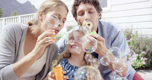 Happy family blowing bubbles in the yard mom dad and child at home Royalty-free stock video