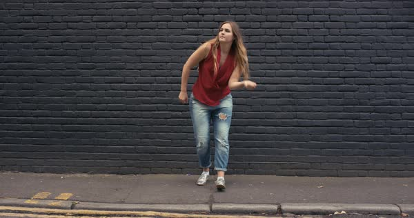 Woman freestyle dancing in front of a black wall in the city Royalty-free stock video