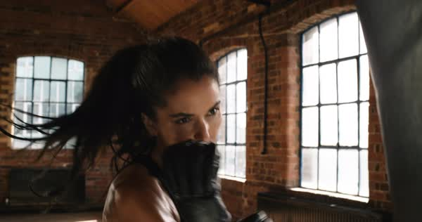 Beautiful kickboxing woman training punching bag in fitness studio fierce strength fit body Royalty-free stock video