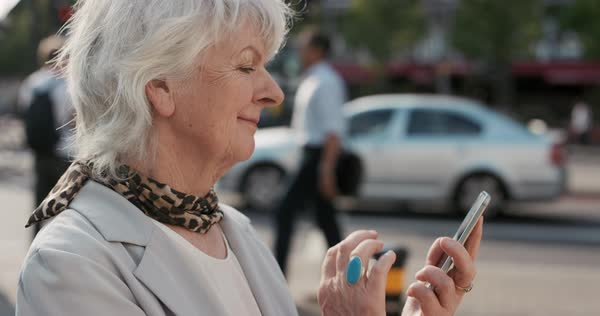 Portrait of happy mature old woman using smart phone sharing social media connection in city, slow motion Royalty-free stock video