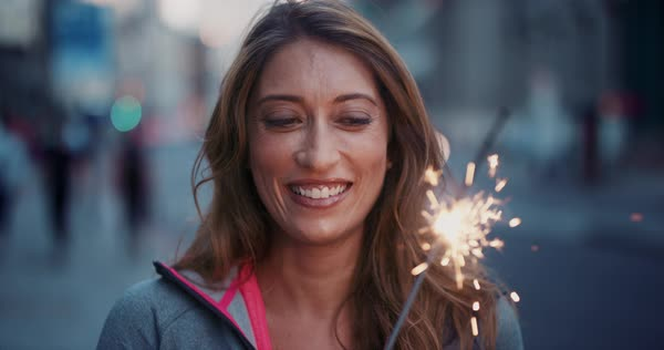 Portrait of happy beautiful fitness woman smiling holding sparkler in city celebrating new year success, slow motion Royalty-free stock video
