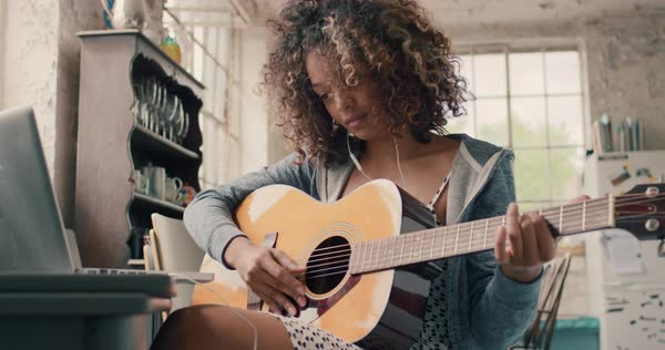 Attractive curly haired young woman sitting on wooden chair at a window wearing a grey hoodie concentrating focused learning to play guitar using laptop computer at home Royalty-free stock video