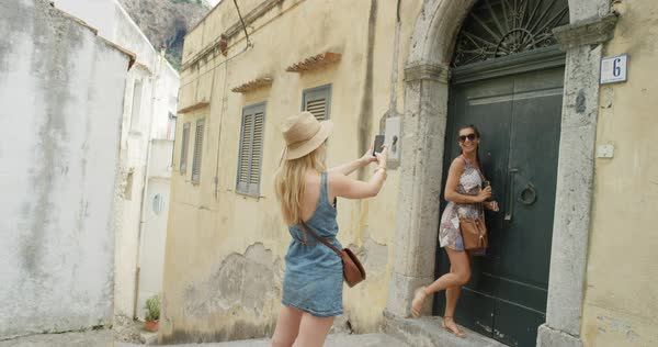 Young woman photographing Italian architecture in small coastal village on vacation Royalty-free stock video