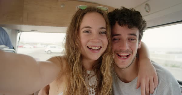 Portrait of of teenage couple taking selfie photograph kissing smiling and laughing in retro campervan on summer road trip adventure Royalty-free stock video