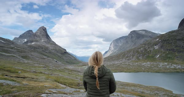 Woman with arms raised on top of mountain looking at view of glacial valley Hiker wearing green down jacket lifting arm up celebrating landscape enjoying vacation travel adventure nature Norway Royalty-free stock video