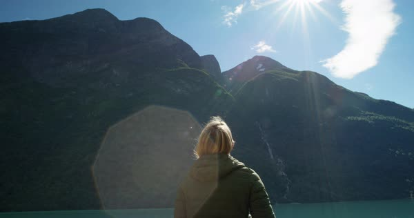 Woman standing at edge of lake looking at view of mountain Camping in scenic landscape enjoying vacation travel adventure nature Norway Royalty-free stock video