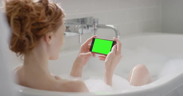 Woman using smartphone touchscreen chroma-key green screen enjoying relaxing bubble bath close-up sharing on digital display Royalty-free stock video