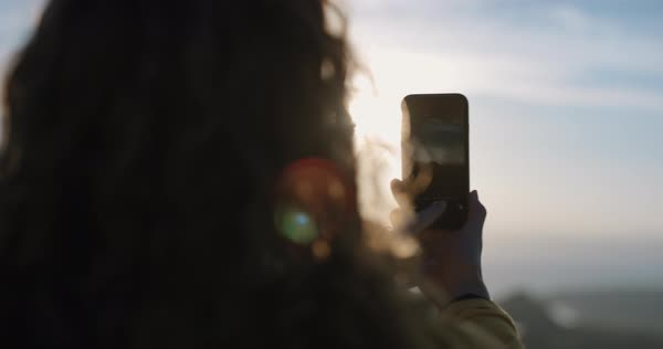 Close-up woman taking photo of sunset with smartphone photographing sunrise picture of ocean view with soft light lens flare landscape nature background enjoying vacation adventure Royalty-free stock video