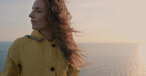 Close-up portrait of young woman with red hair blowing in wind looking at sunset over ocean wearing yellow raincoat trekking in Scotland slow motion Royalty-free stock video