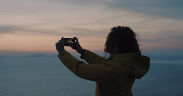 Photographer woman taking photograph of sunset ocean view with smartphone young photographing scenic landscape nature background enjoying vacation  Royalty-free stock video