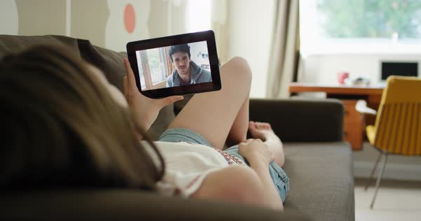 Young woman having video chat holding smartphone webcam lying on sofa at home chatting to friend Royalty-free stock video