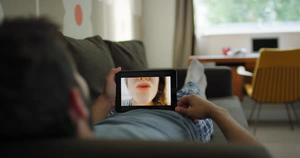 Young man having video chat holding smartphone  webcam chatting to girlfriend lying on sofa relaxing at home in modern apartment Royalty-free stock video