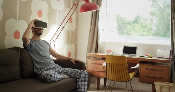Young man wearing virtual reality headset sitting on sofa at home watching 360 video in retro styled modern apartment Royalty-free stock video