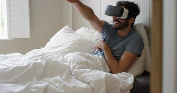 Man lying in bed wearing virtual reality headset gaming playing game watching 360 video Royalty-free stock video
