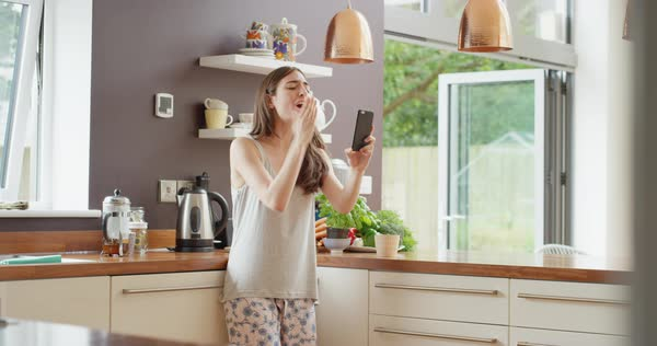 Young woman having video chat at home in kitchen holding smartphone  blowing kiss at webcam chatting to friend Royalty-free stock video