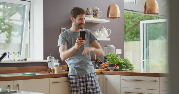 Man having video chat at home in kitchen holding smartphone explaining funny story webcam chatting to friend Royalty-free stock video