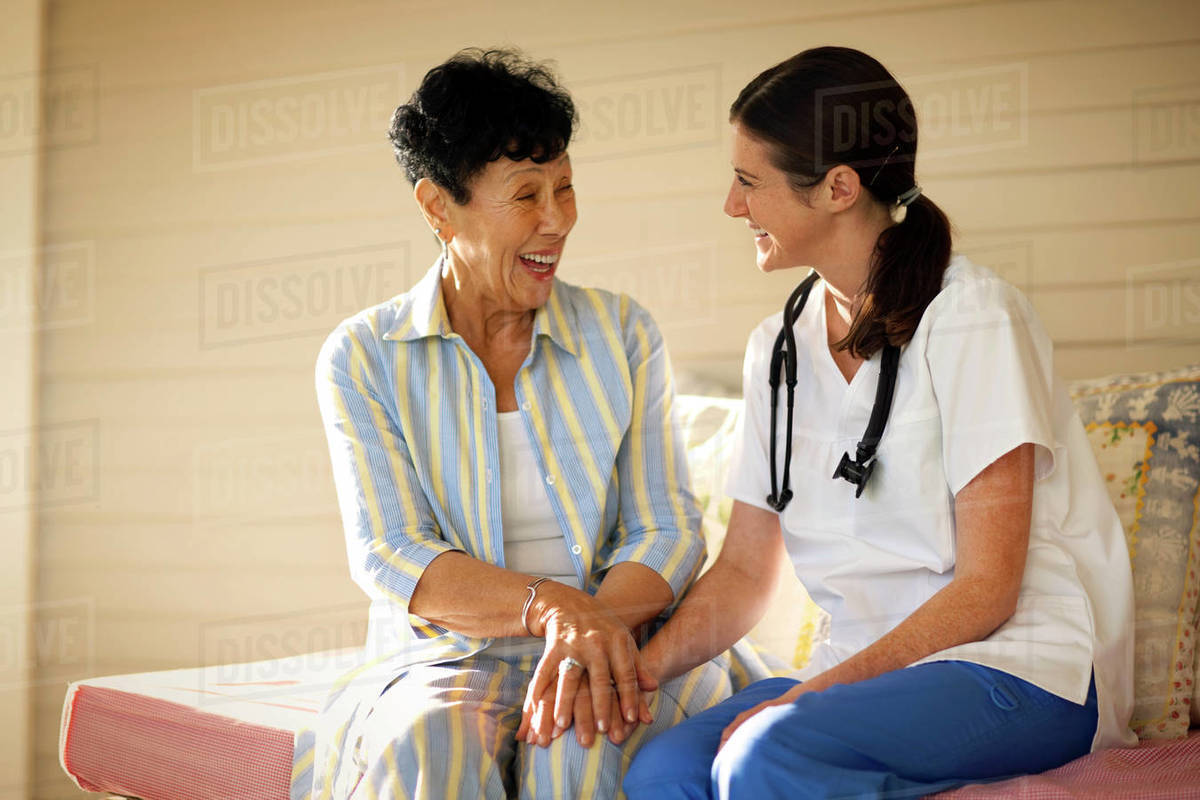 Young female nurse sitting with an elderly patient on her verandah, Royalty-free stock photo