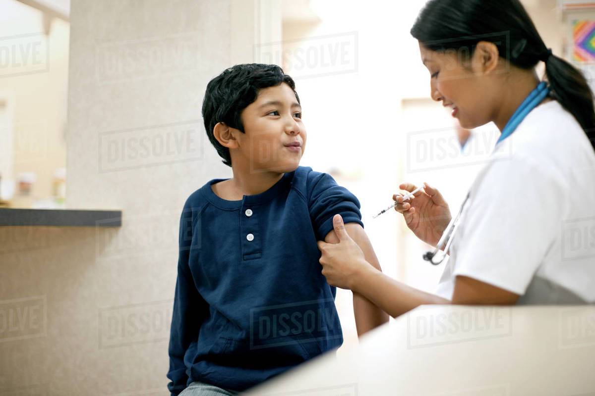 Nurse giving vaccine to her young patient. Royalty-free stock photo