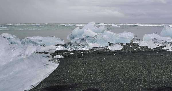 Hyper-lapse icebergs on a black sand beach under a cloudy sky. Jokulsarlon Glacier Lagoon, Iceland Royalty-free stock video