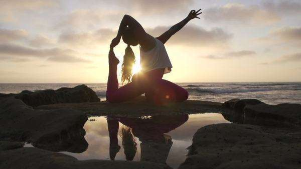 Woman practicing difficult advanced yoga pose at sunset with lens flare Royalty-free stock video
