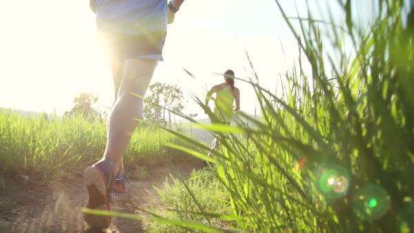 Active couple running outside into sun with lens flare Royalty-free stock video