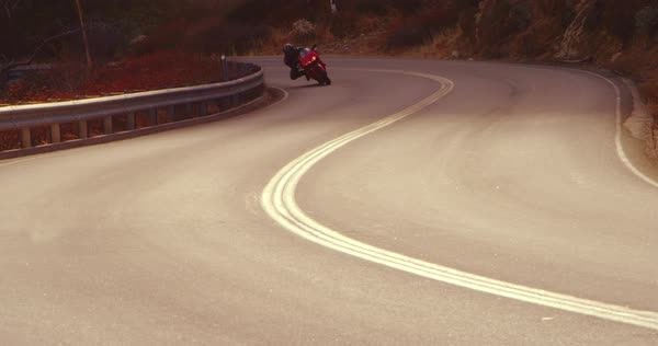 Extreme motorcyclist riding sport bike on turn on a curvy road filmed in slow motion  Royalty-free stock video