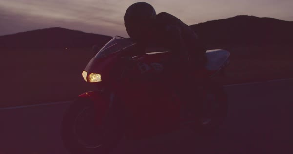 Motorcyclist riding his motorcycle down straight country road going a high speed  at sunset with headlights on Royalty-free stock video
