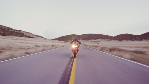 Motorcyclist racing his motorcycle down straight country road going a high speed  at sunset with headlights on Royalty-free stock video