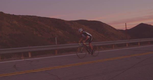 Slow motion fit man exercising on road bike riding up hill at sunset Royalty-free stock video