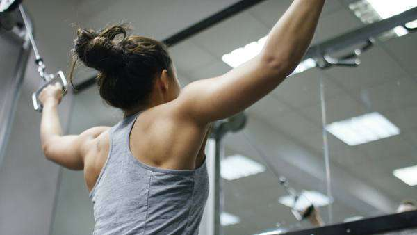 Young woman using a cable pulley machine in the gym Royalty-free stock video