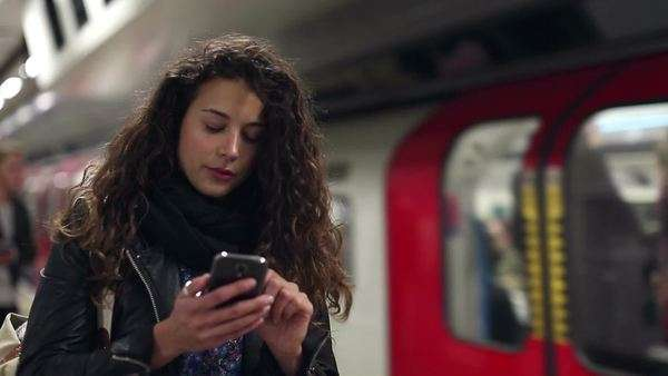 Attractive young woman using her smartphone as a subway train approaches Royalty-free stock video