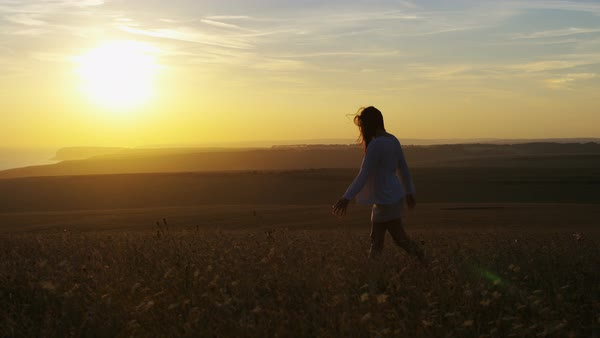 Wide shot of young woman walking through a field at sunset by herself Royalty-free stock video