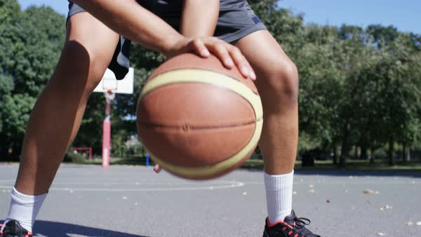 Basketball player dribbling the ball on an outdoor basketball court Royalty-free stock video