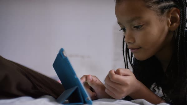 Young girl using a digital tablet whilst relaxing on her bed Royalty-free stock video
