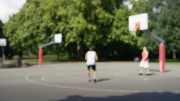 Blurred background of two people paling basketball on an outdoor court, great for text Royalty-free stock video